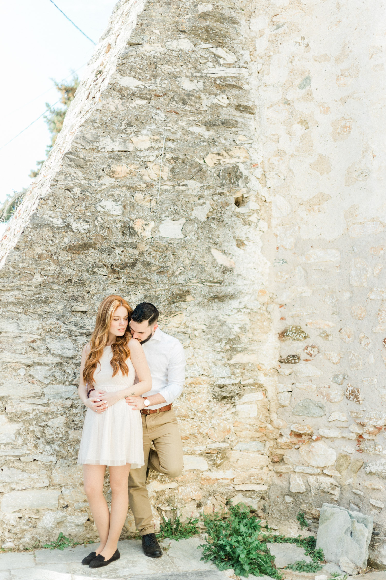 couple posing in front of an old rocky wall while engagement fine art session in Halkidiki, Greece