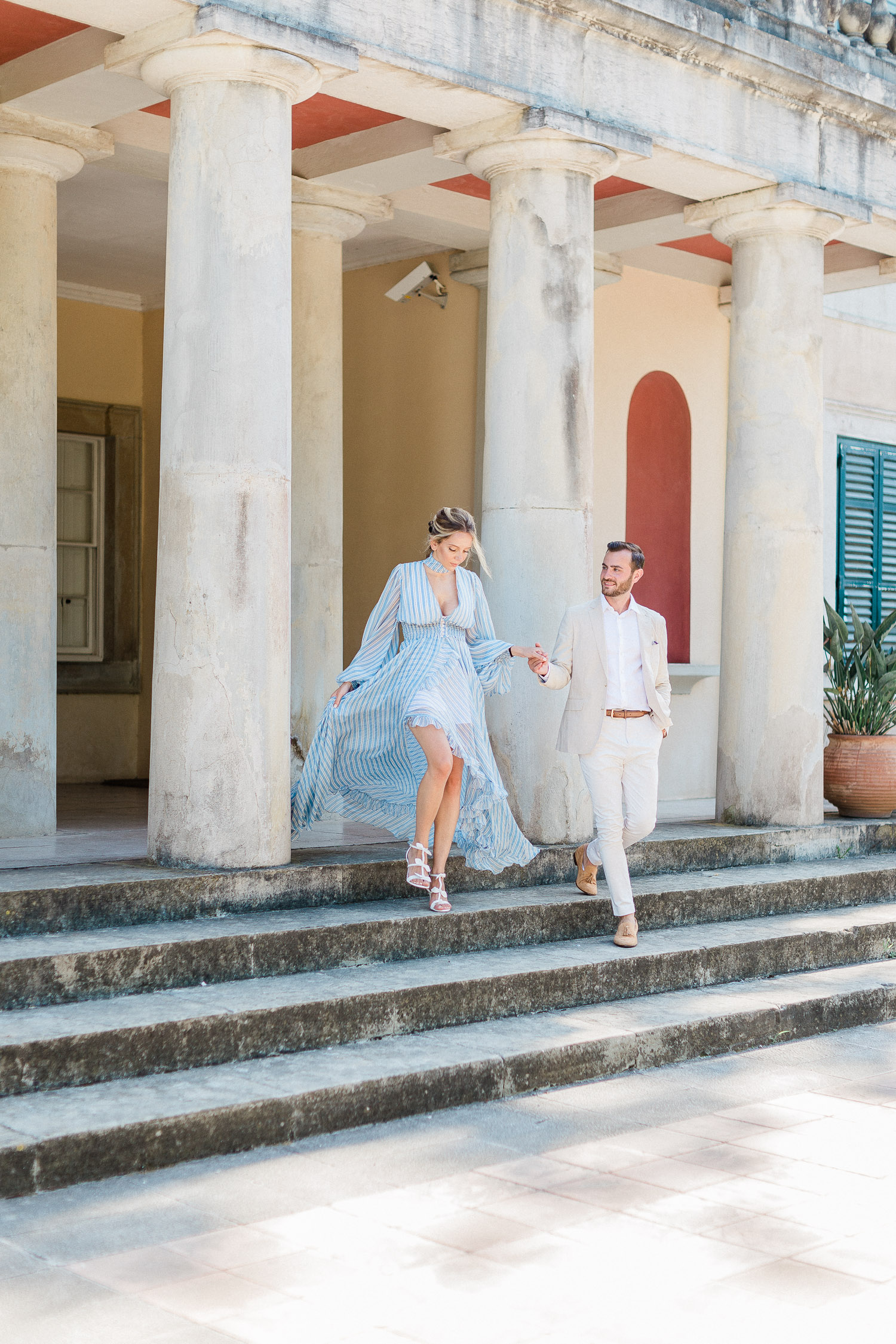this chic couple walking down the Mon Repos palace at Corfu while their fine art wedding engagement session
