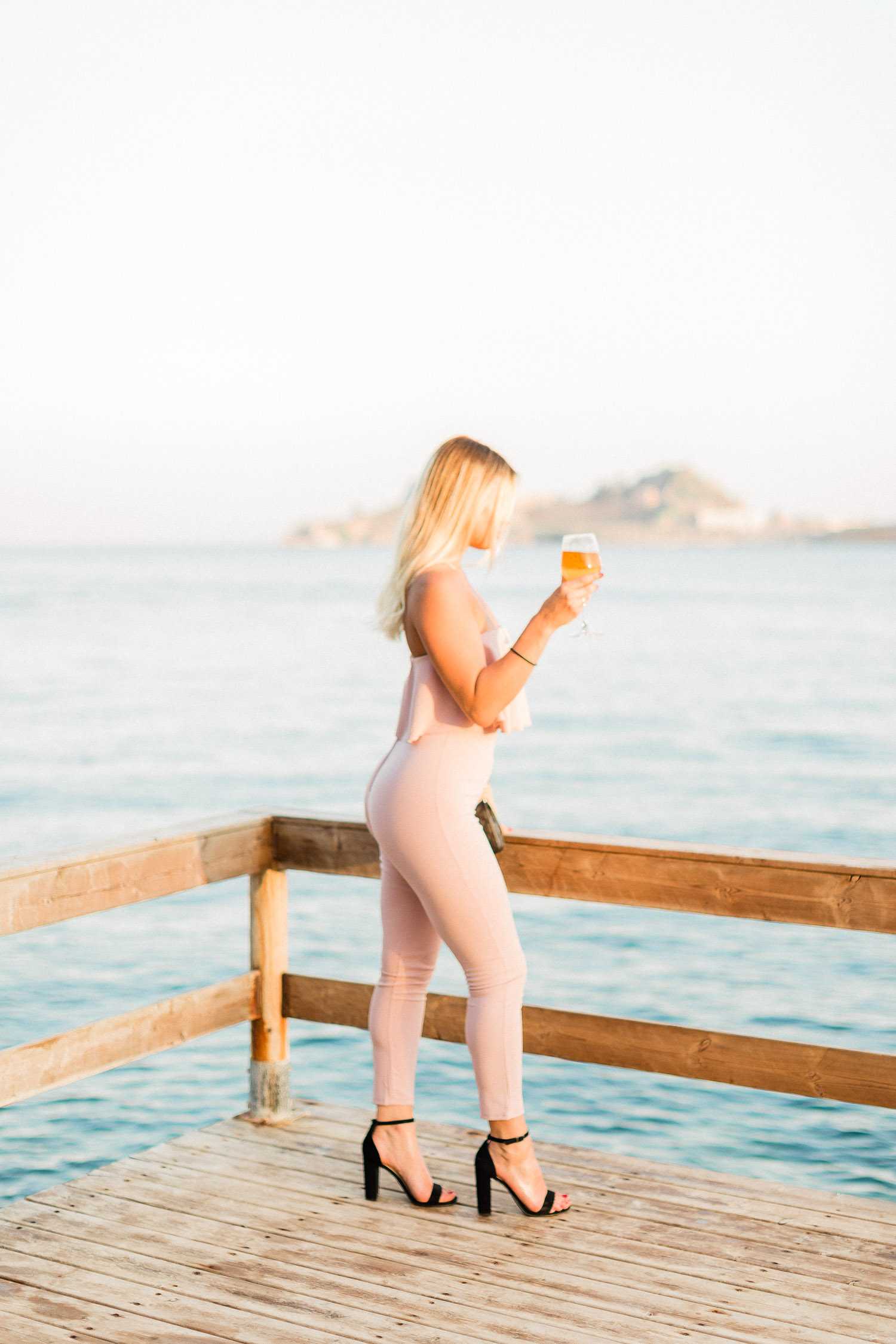 wedding guest while drinking her cocktail at Corfu island