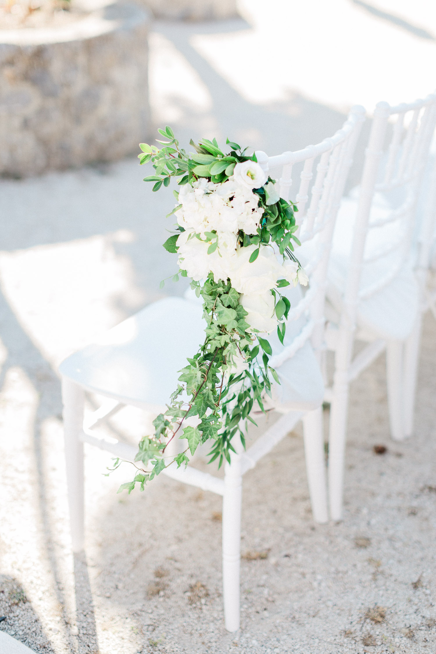 all white chair floral details at wedding ceremony set up
