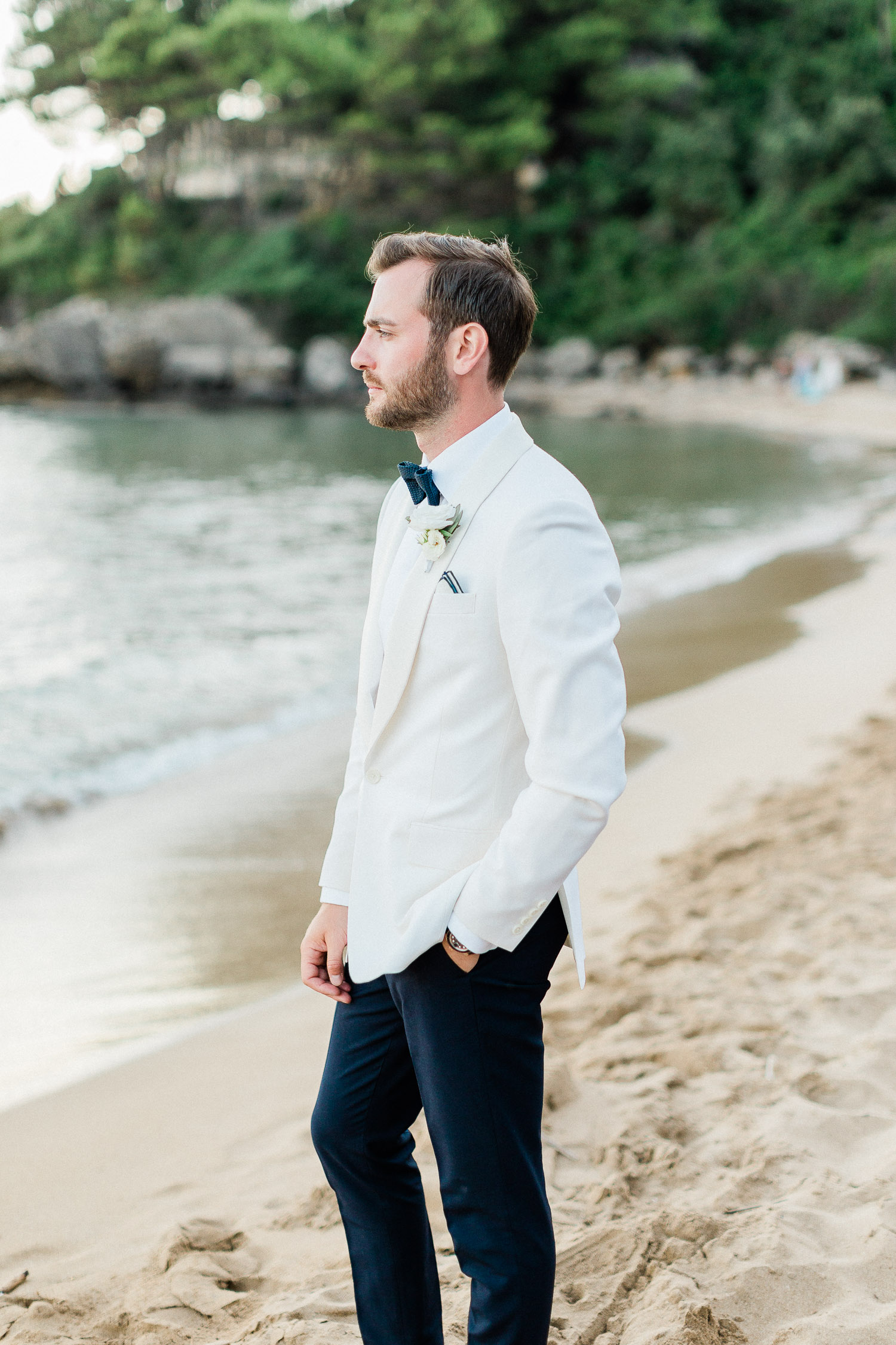 groom poses on the beach after the wedding