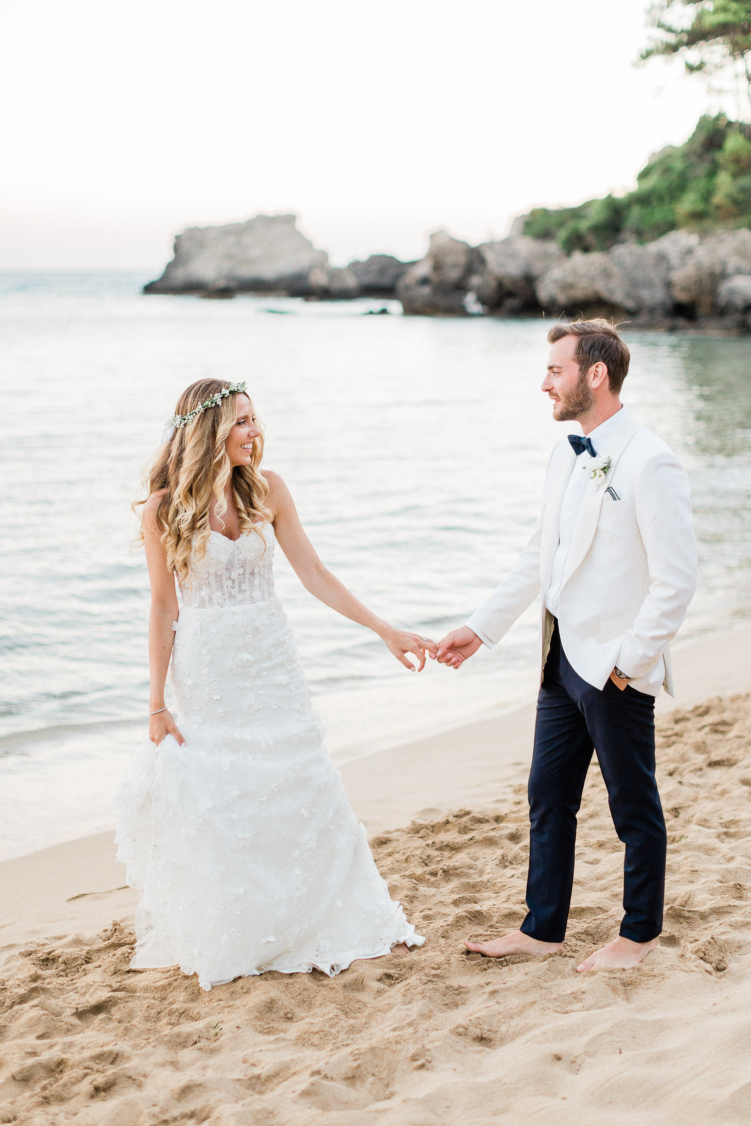 bride and groom walking at Corfu beach after ceremony