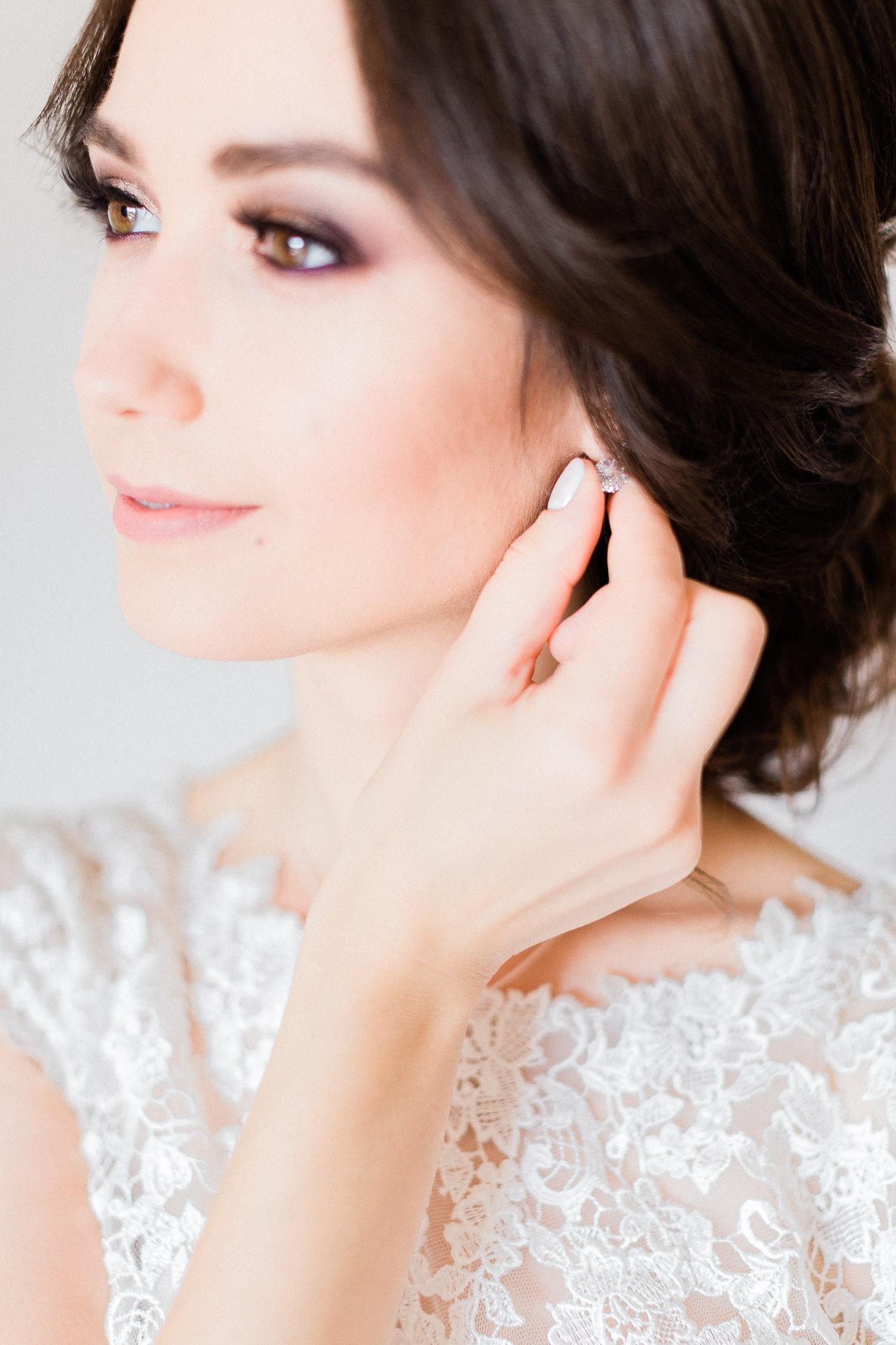 bride wearing gently a pair of diamond earrings