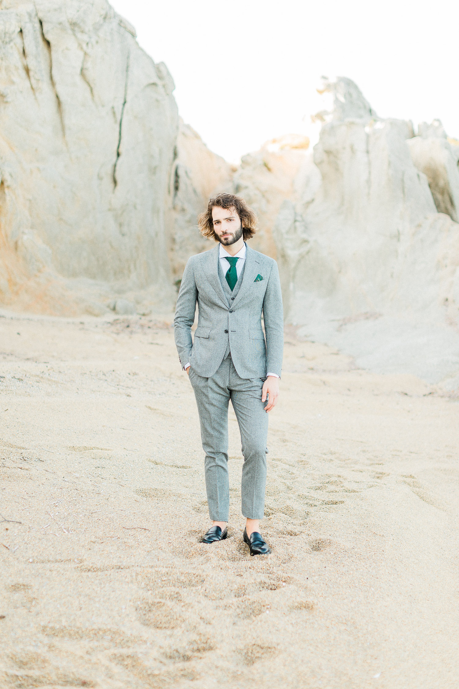 a stylish groom wearing grey tuxedo with green details