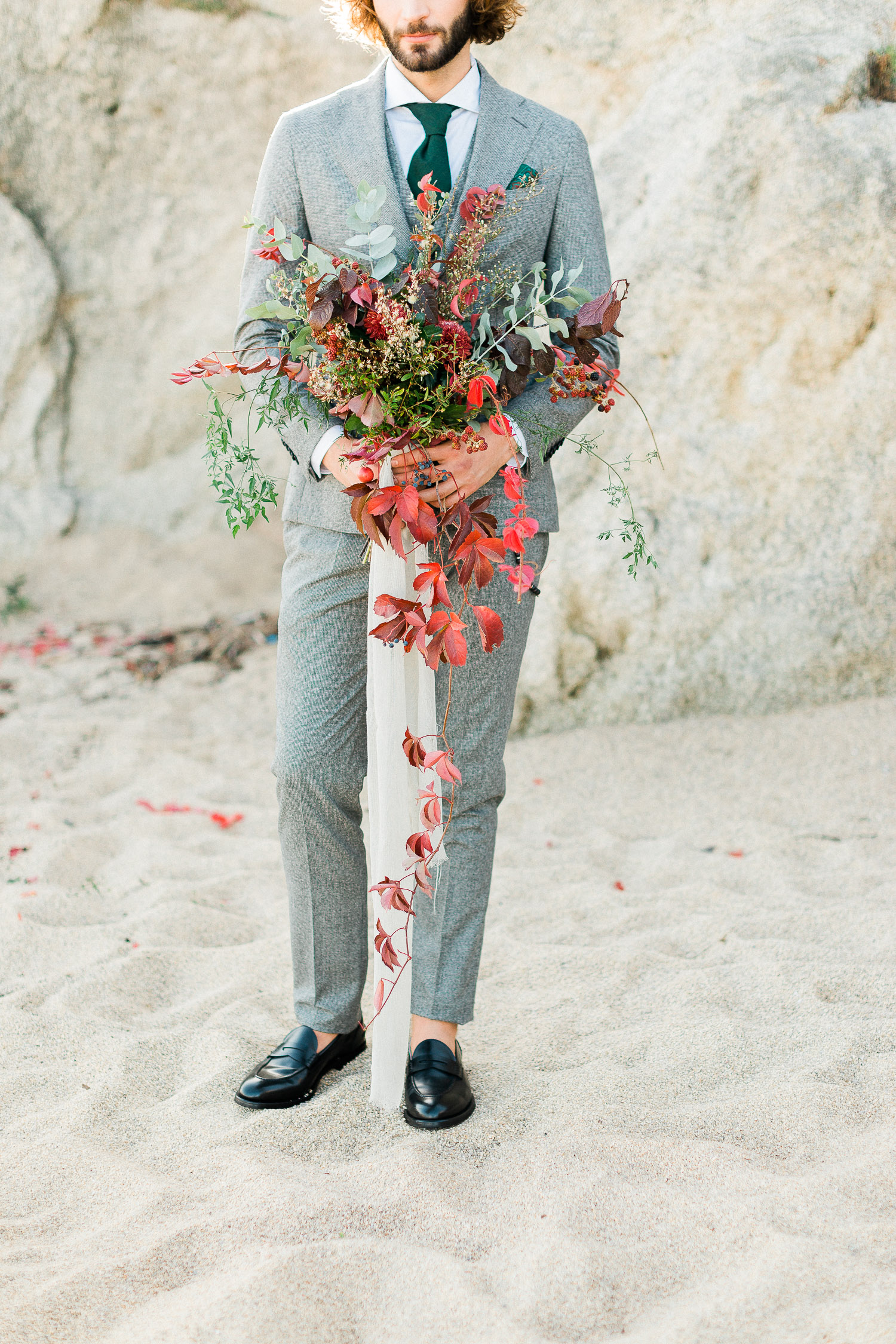 a stylish groom wearing grey tuxedo with green details while holding a lush florals bouquet