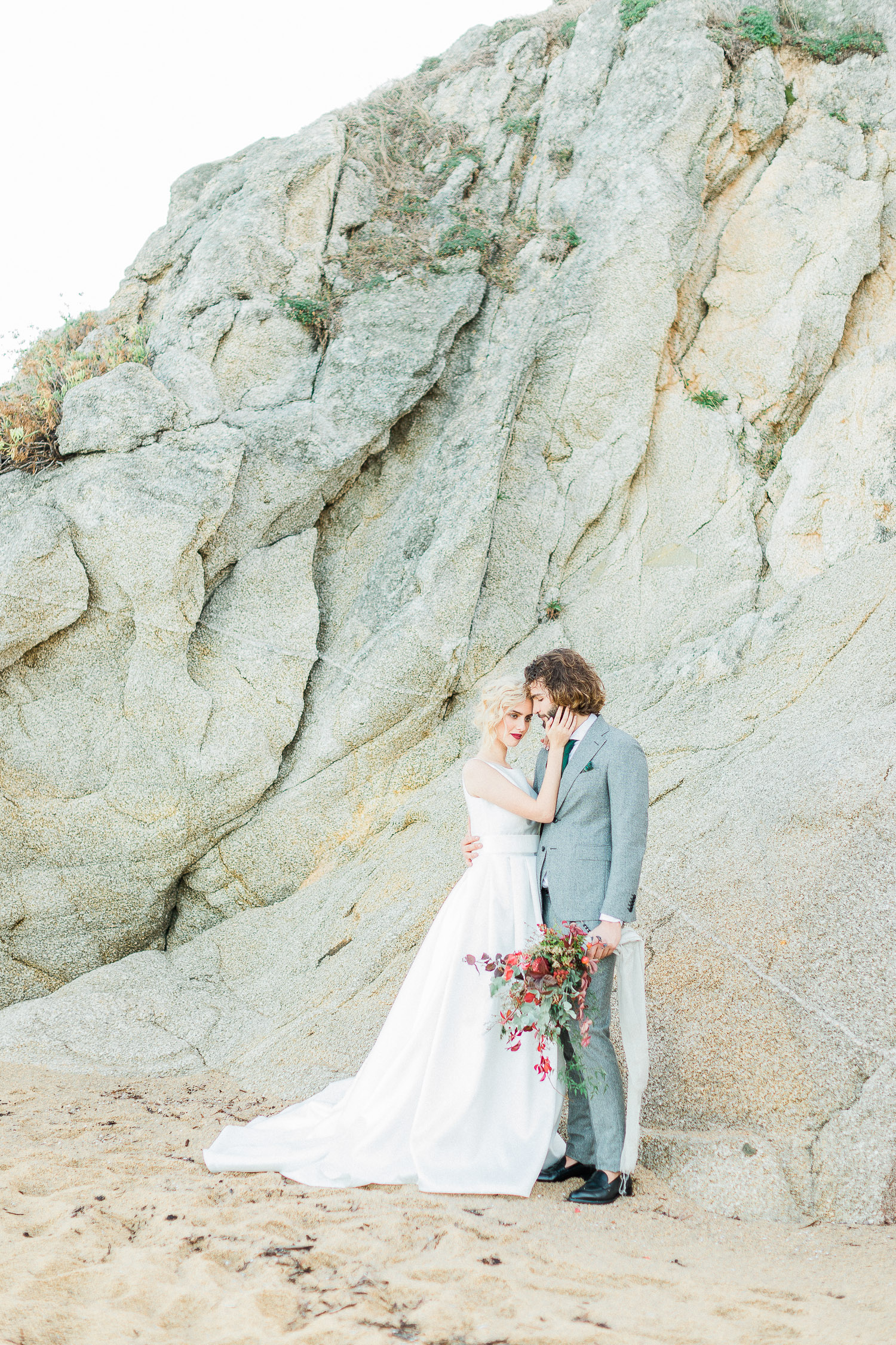 a romantic couple portrait on a rocky beach elopement at in Greece