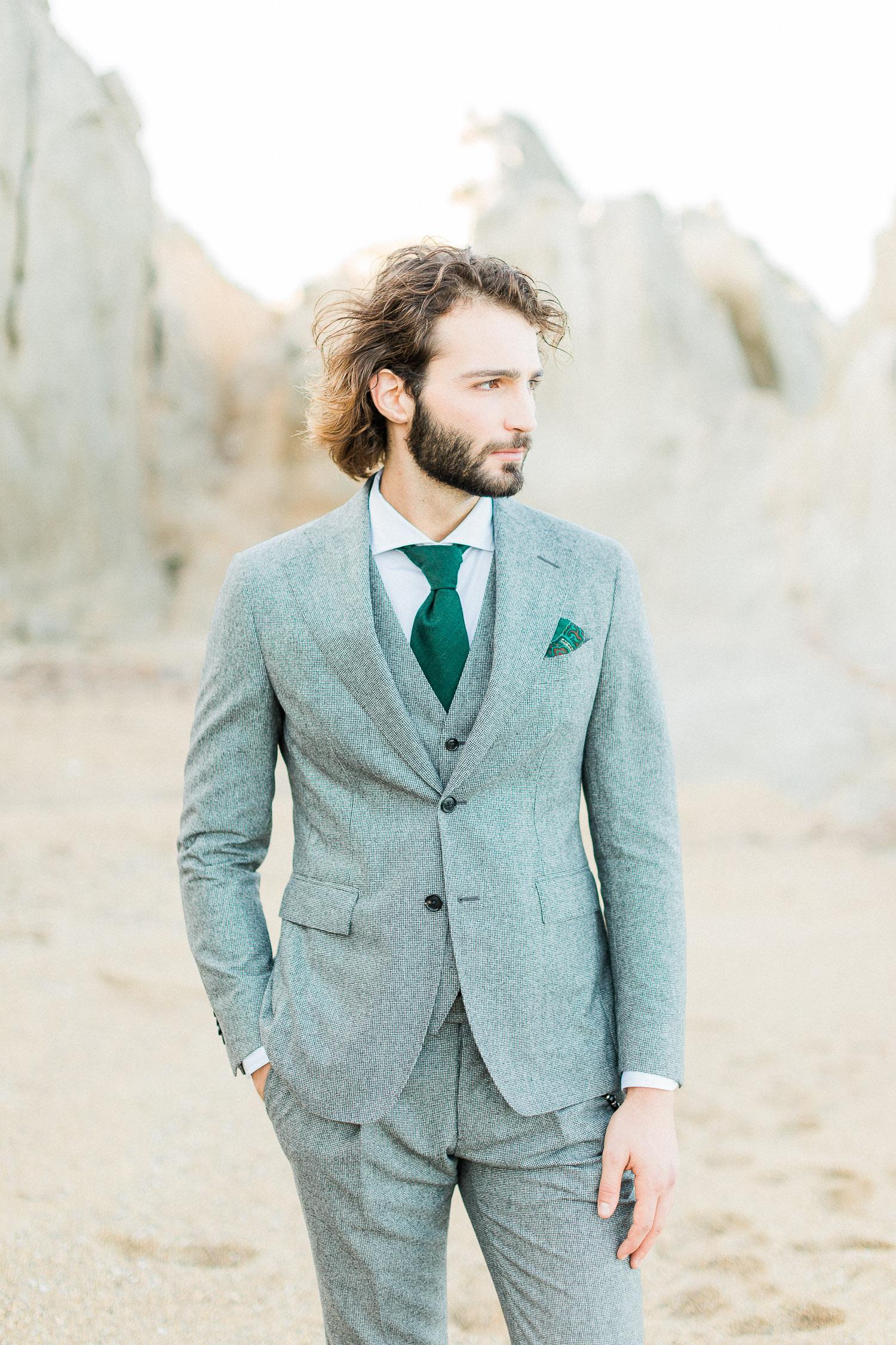 groom's portrait wearing a grey tuxedo