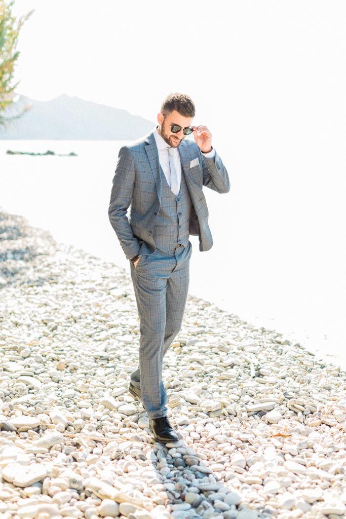 groom portrait walking on the beach while a Corfu wedding