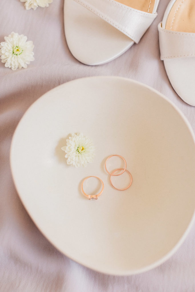 wedding rings flat lay styled with beautiful all white flowers