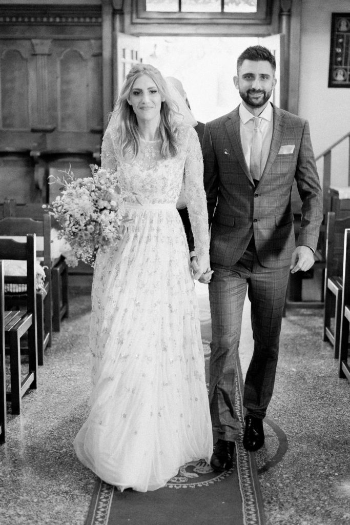 black & white portrait of a couple while they enter in church