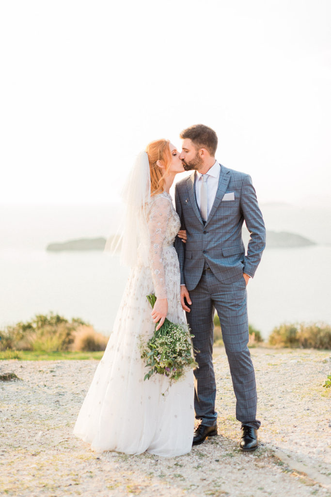 fine art bride & groom portrait kiss each other with spectacular view at Ionian sea