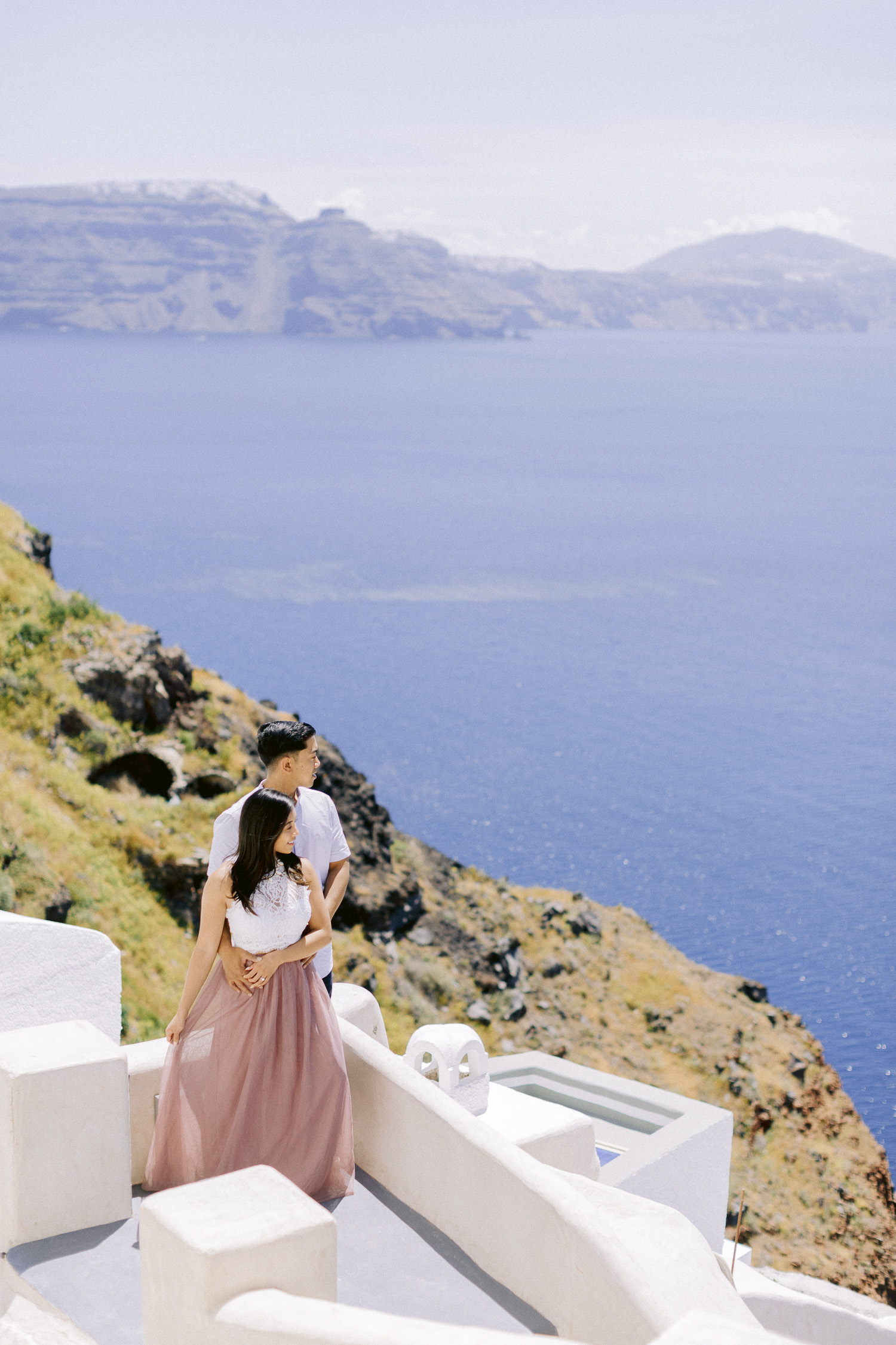 Couple enjoy the view of Santorini while their engagement shoot