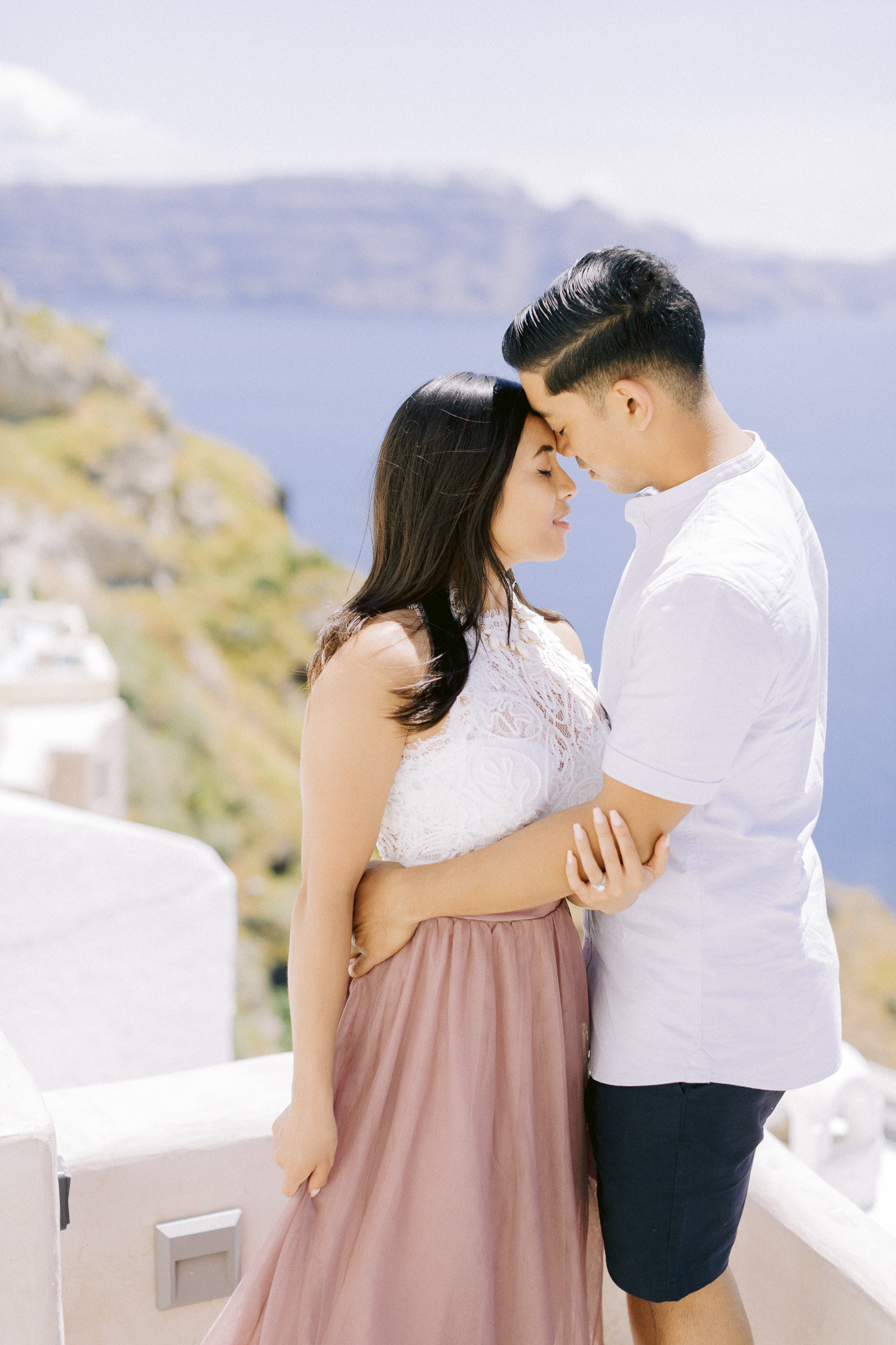 Tender moment between a couple with a backdrop of Santorini