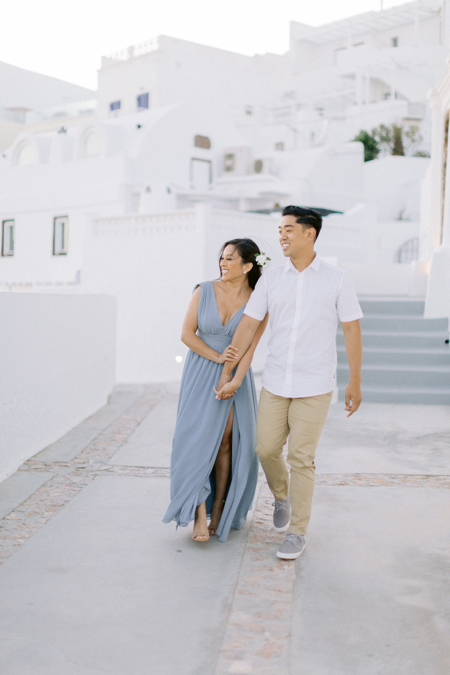 Glamorous couple walk in between beautiful white houses of Santorini