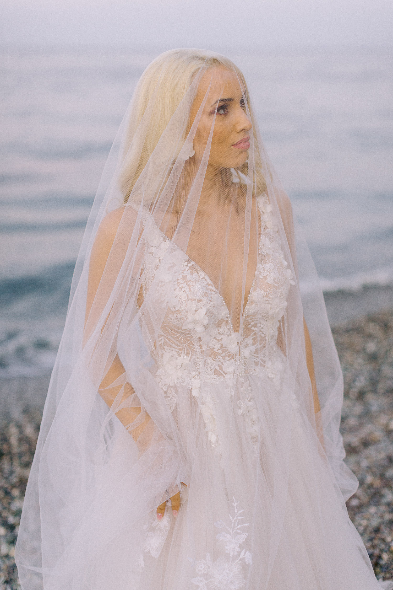 romantic coastal wedding stunning bridal portrait wearing her long lace veil
