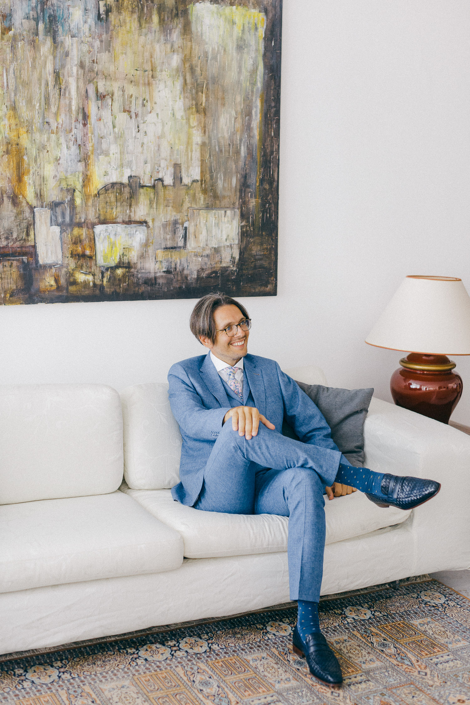 Stylish groom on a total blue attire enjoying some moment at a luxury living room