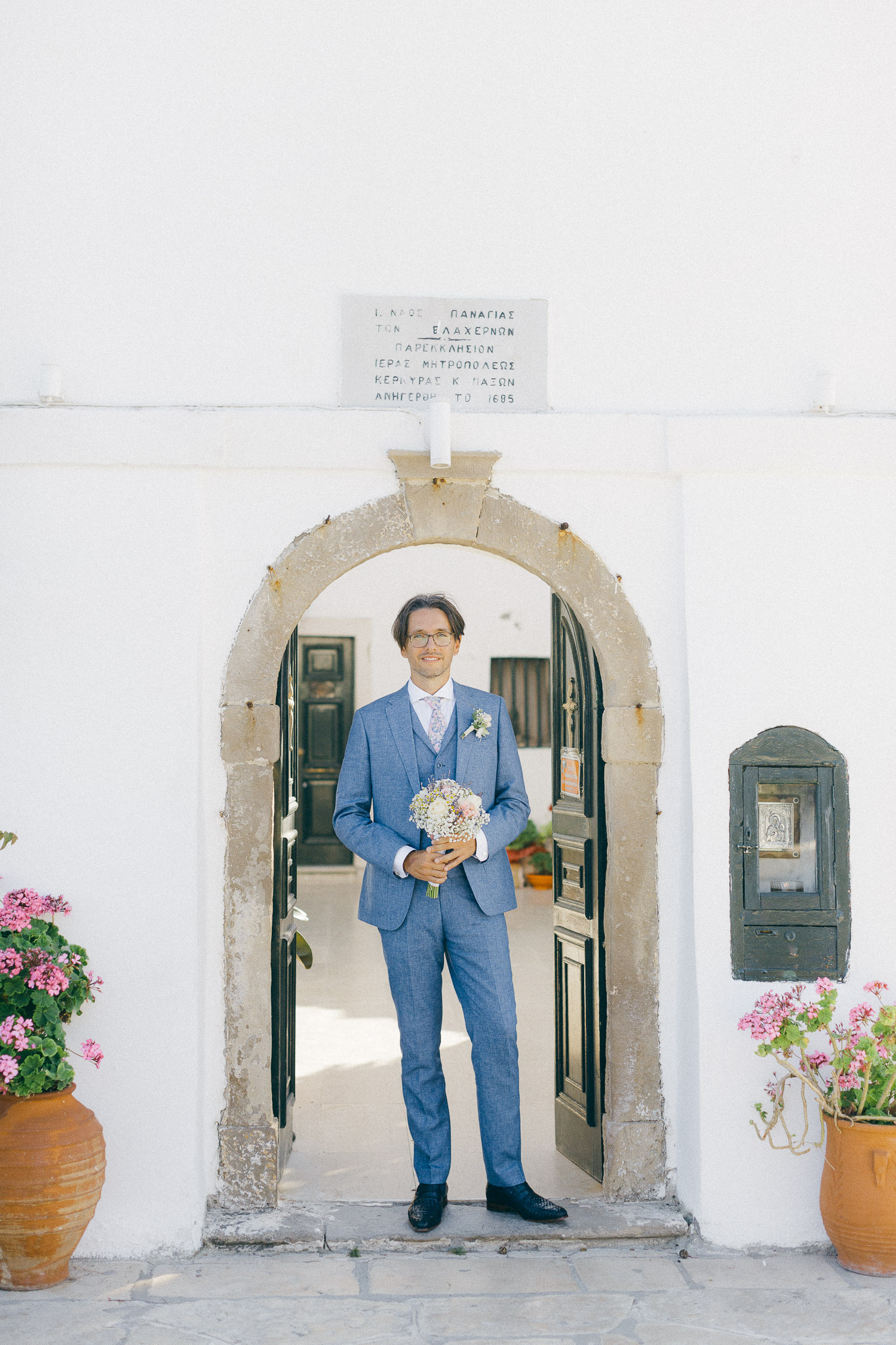 Groom standing at Vlacherena church entrance and waiting for the bride while Old World micro wedding in Corfu Island