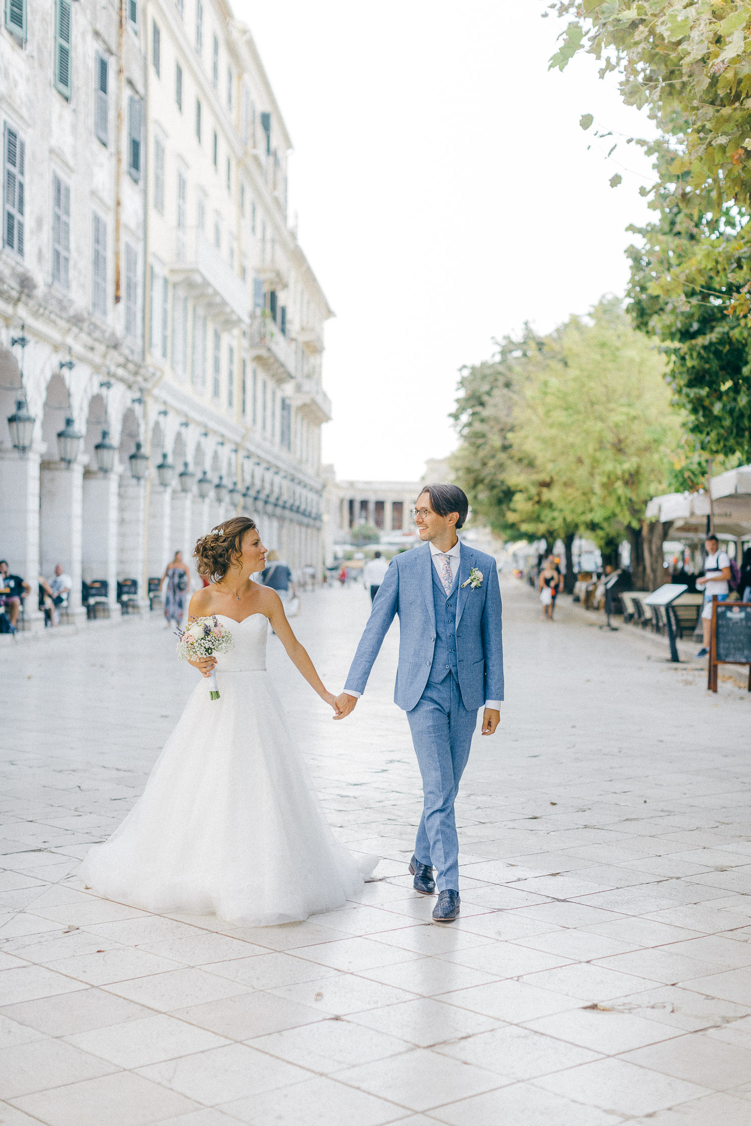 Bride and groom walking through Liston square in Corfu while post ceremonial portraits
