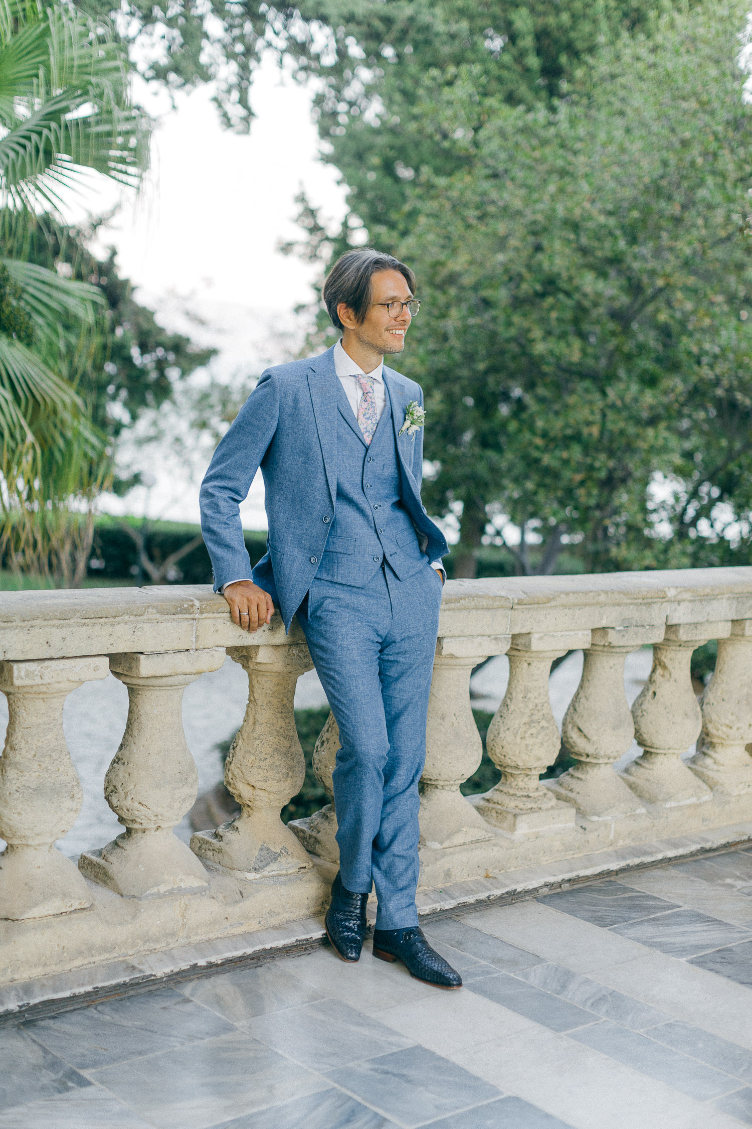 Groom poses out of St Michael Palace in Corfu while an Old World micro wedding in Corfu Island