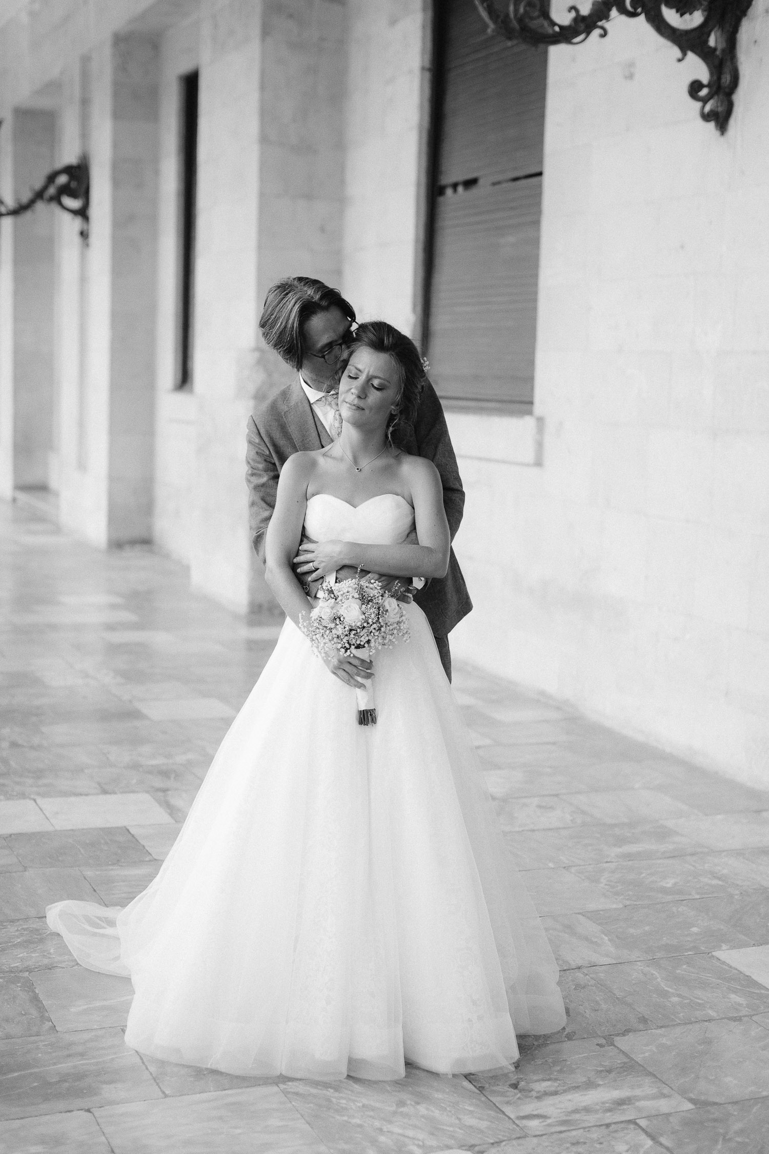 Bride and groom posing full of love out of Corfu palace