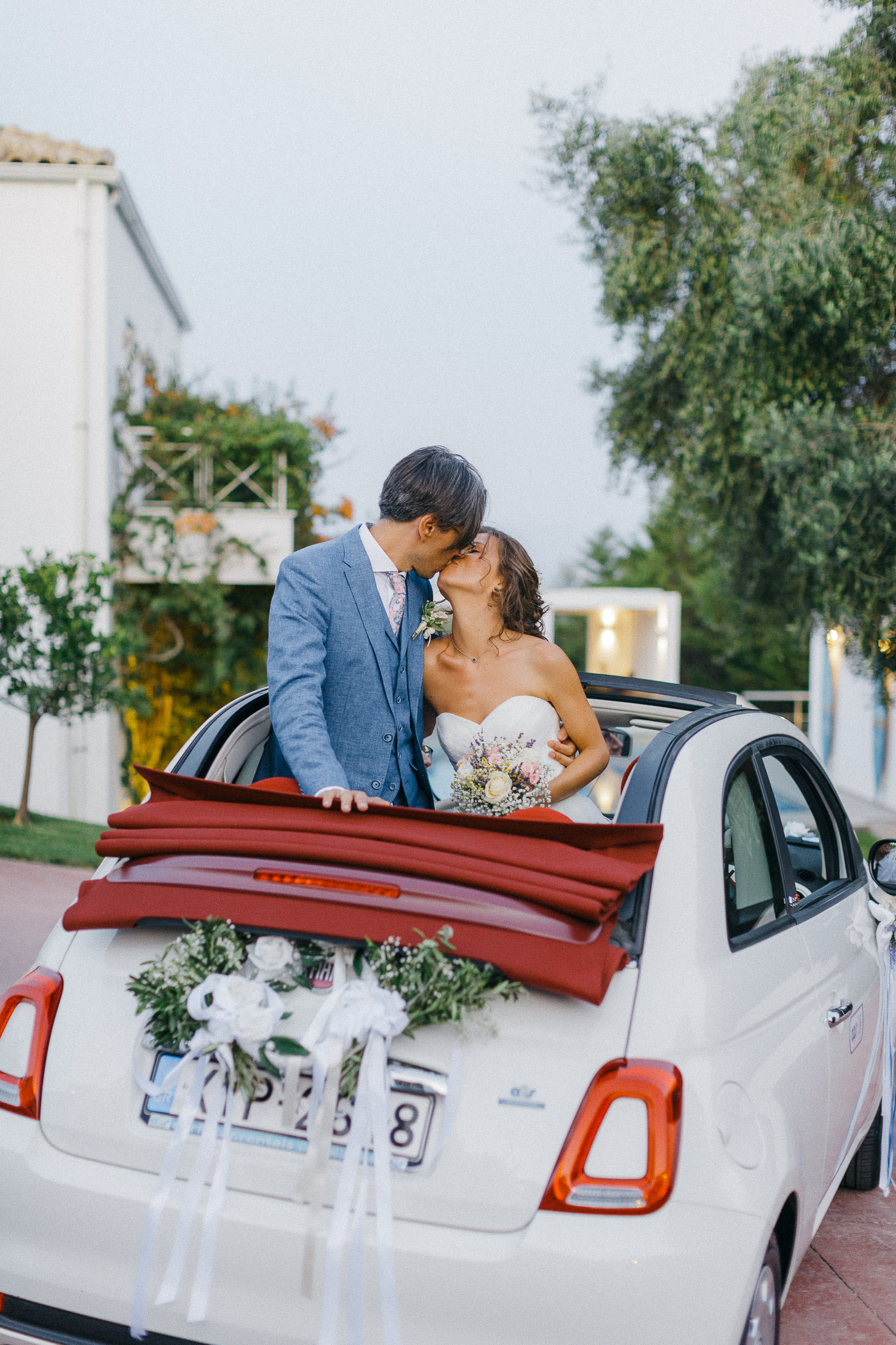 Couple kissing inside Fiat 500 wedding wheels while arriving at wedding venue