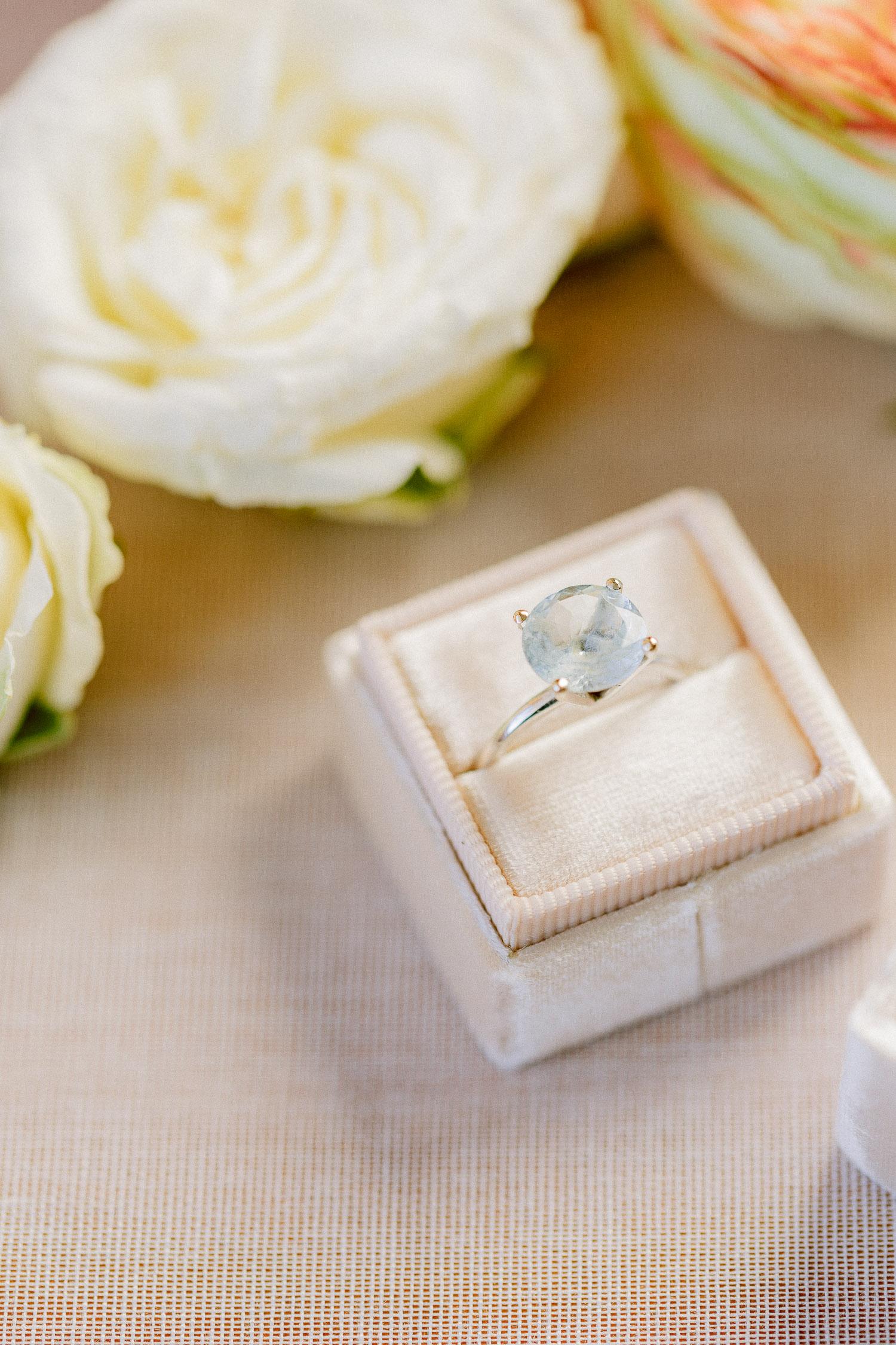 Round cut engagement ring detail in pink velvet ring box